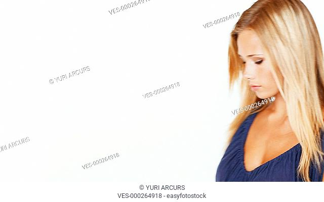 Gorgeous young blonde walking past a white background with her arms folded and smiling shyly at the camera