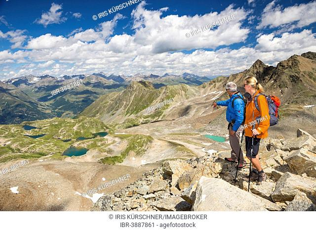 Two hikers on the Fuorcia da Barcli pass, overlooking the Macun Lakes, Swiss National Park, Graubünden, Switzerland