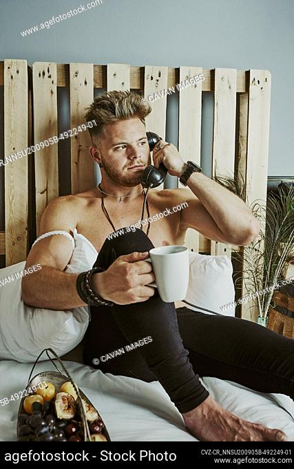 a young man sitting on the bed talking on the landline phone and drinking coffee