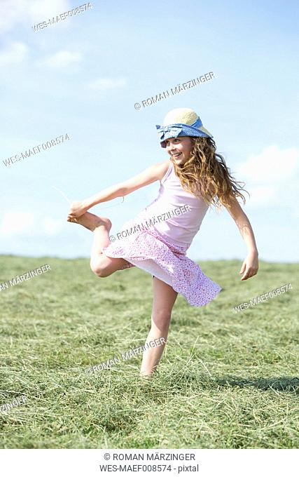 Germany, Bavaria, Young girl on meadow with hay