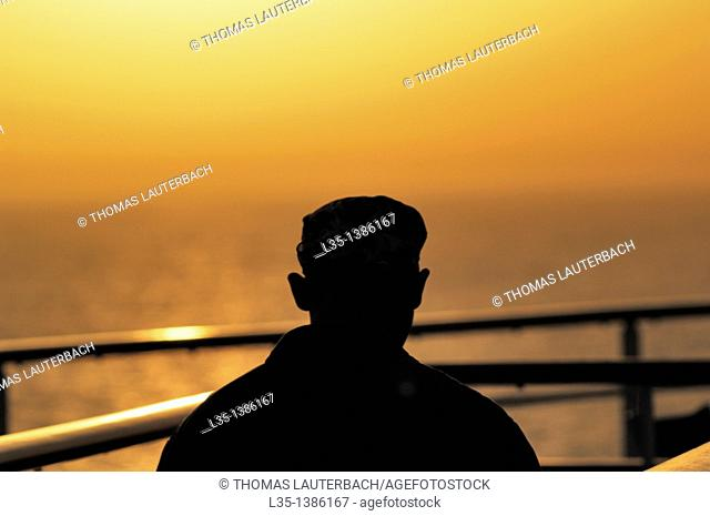 A man looks at hazy sunset over the Mediterranean