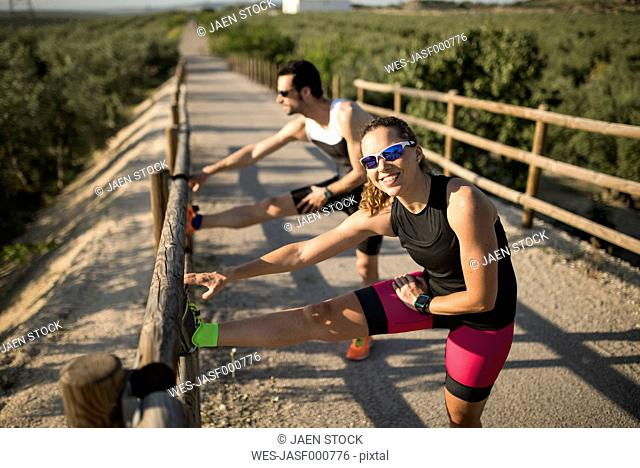 Smiling sportive woman and man stretching on a bridge