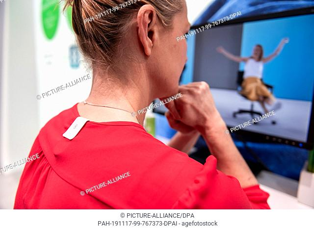17 November 2019, North Rhine-Westphalia, Duesseldorf: Model Anne Apitzsch sits in front of a television set with the clip of the Beurer company during a tour...