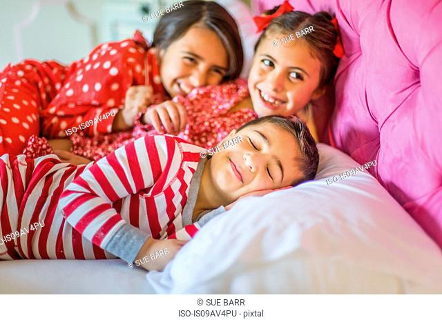 Cute boy and two sisters lying in bed giggling