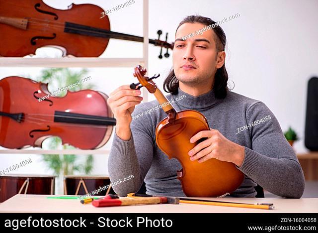Young male repairman repairing violin in workshop