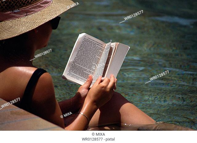 Adult woman reading book at poolside