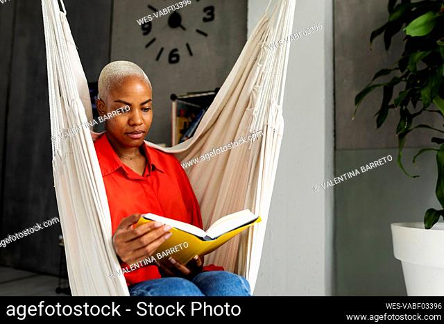 Woman sitting in hammock reading book