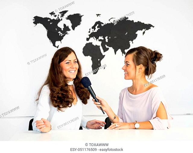 Two girls reporters twins are reporting from a white studio with a map of the world on the background