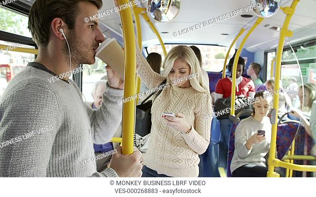 Interior of crowded bus with passengers listening to music and using mobile phone.Shot on Sony FS700 in PAL format at a frame rate of 25fps