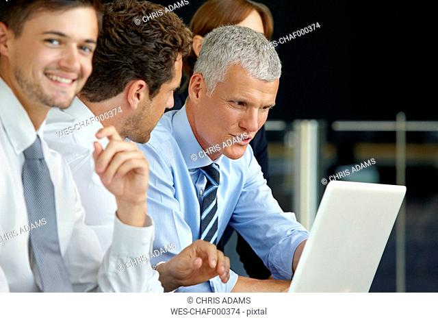 Businesspeople working on laptop