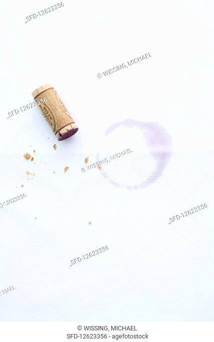 A cork from a red wine bottle on a piece of white paper