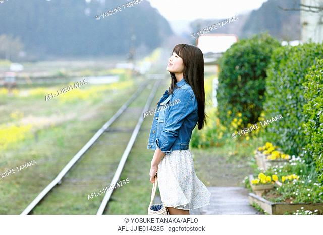 Attractive young Japanese woman at local train station in the Japanese countryside