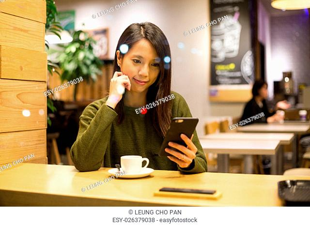 Woman use of smart phone in cafe at night