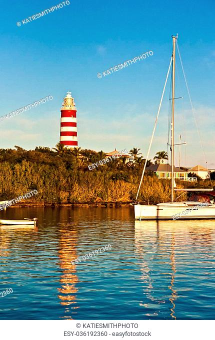 Red and white candy cane striped lighthouse on Elbow Cay, Abaco, Bahamas, Hope Town. Several sailboats are anchored in calm blue water, below the lighthouse
