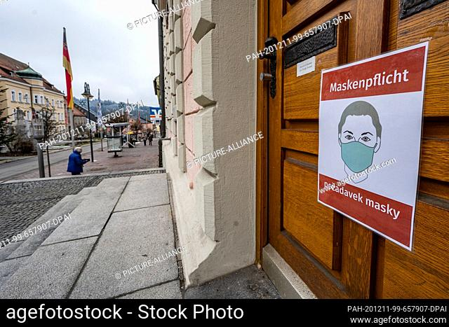 """11 December 2020, Bavaria, Zwiesel: A sign with the inscription """"""""Mask duty"""""""" in German and Czech is attached to a door. The district of Regen is still a Corona..."""