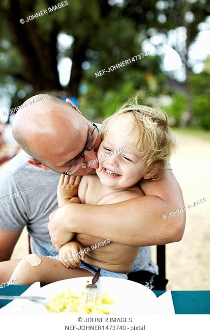Father kissing laughing son