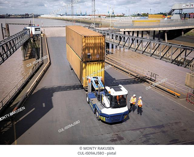 Elevated view of shipping container and truck on ramp to ship