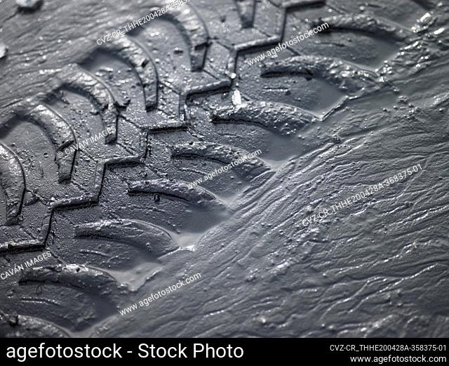 close up of SUV tyre tracks in grey mud