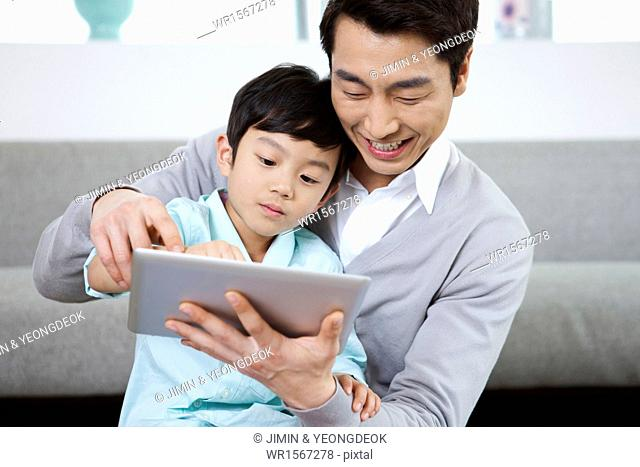a father and a son using a tablet device in the living room