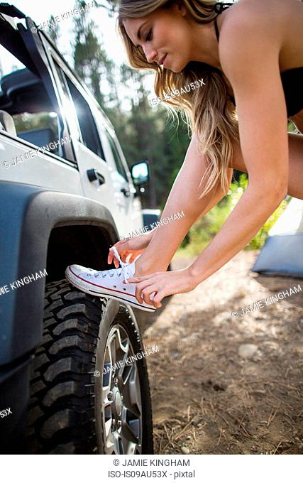 Young woman tying trainer laces on jeep, Lake Tahoe, Nevada, USA