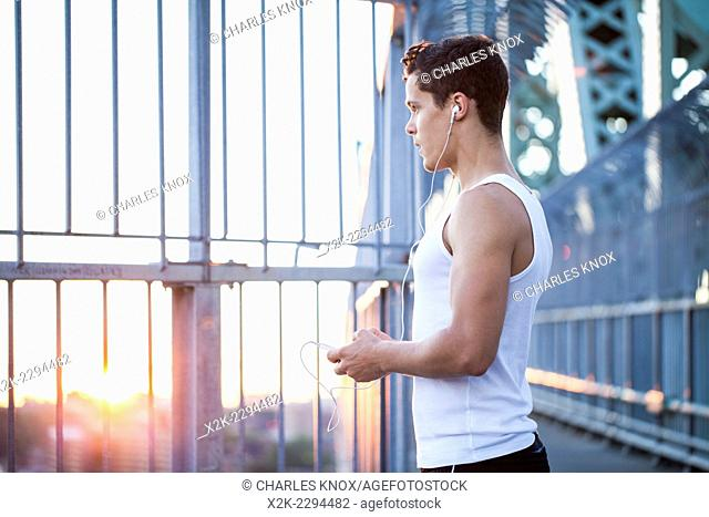 Young man Young man resting after running while listening to music in urban city setting at sunset