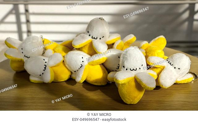 Miniature Stuffed Bananas/ Keychain/ Soft Toys with Cute Faces on Wooden Table in the Sun - Outdoors