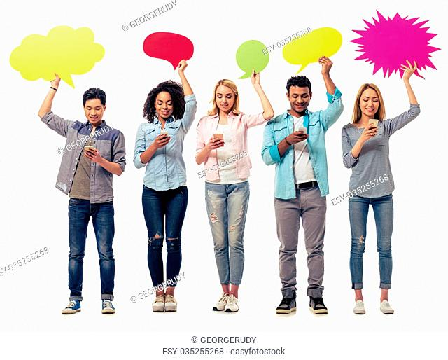 Young people of different nationalities with speech bubbles are using smartphones and smiling, isolated on white background