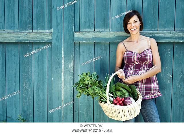 Germany, Bavaria, Woman standing in front of barn door, holding basket with fresh vegetables, smiling, portrait