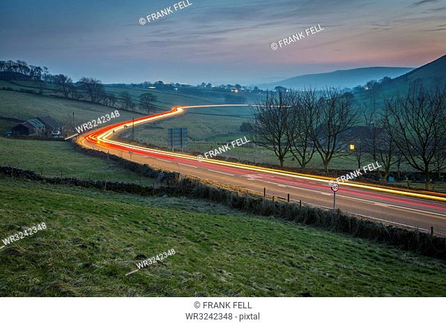 View of vehicle trail lights on A623 at Sparrowpit at dusk, Peak District National Park, Derbyshire, England, United Kingdom, Europe