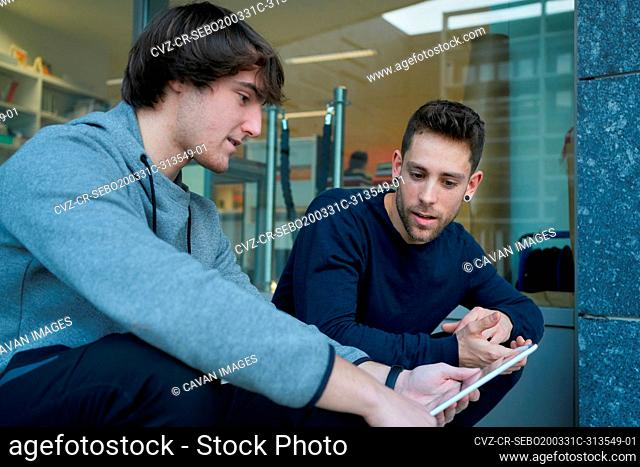 Front view of two young men talking sitting on a city staircase and lo