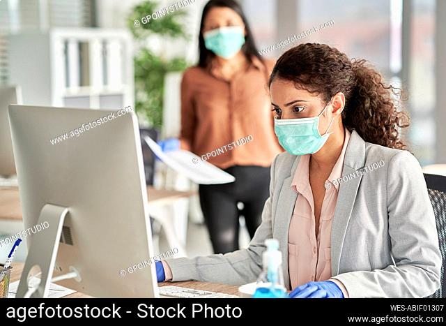 Young female professional wearing protective face mask working on computer at work place