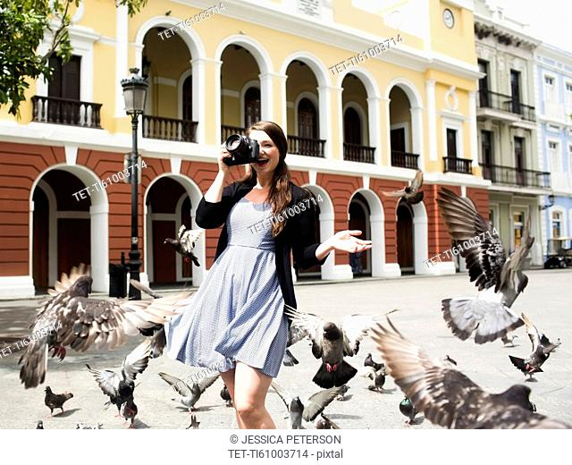 Puerto Rico, San Juan, woman on square among pigeons