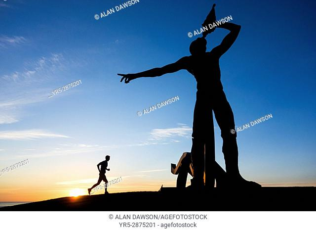 Las Palmas, Gran Canaria, Canary Islands, Spain. A jooger stretches in pre dawn light near sculpture of Greek God, Triton ( son of Poseidon and Amphitrite )...