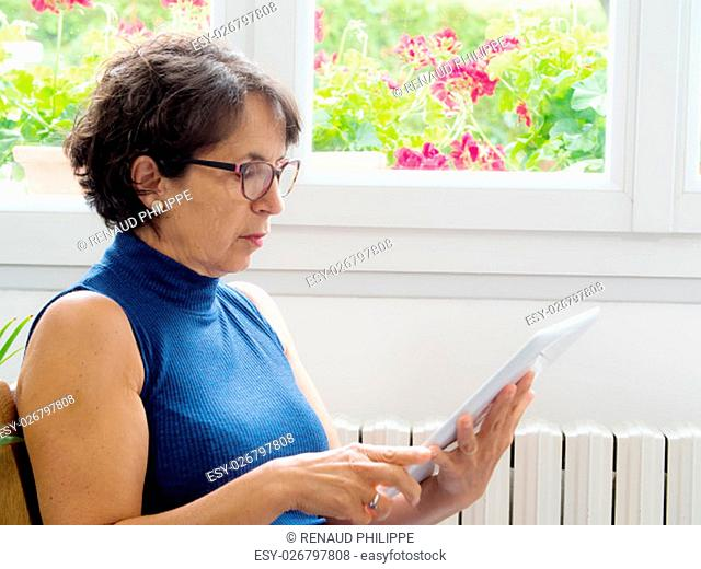 portrait of a mature woman with a digital tablet