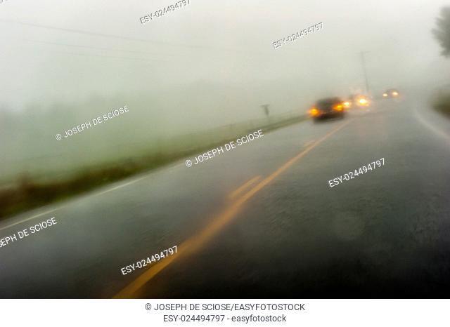 A wet 2 lane paved country road fading to the horizon with on-coming traffic during a rain storm in southern Alabama, USA