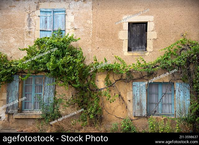 window with old blue shutters in France