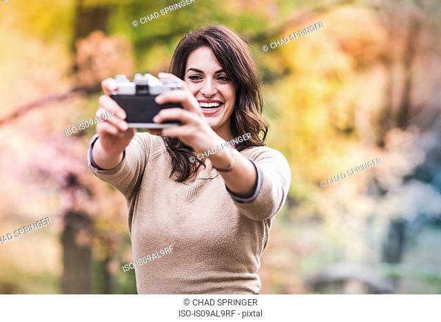 Young woman taking selfie with SLR camera in autumn forest