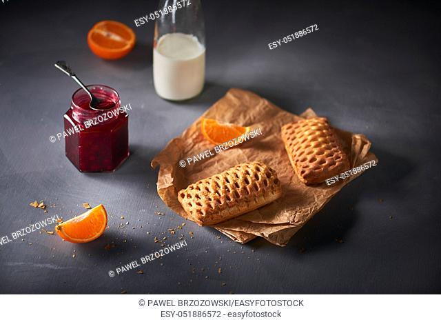 Buns with cranberry jam, bottle of milk and pieces of tangerine