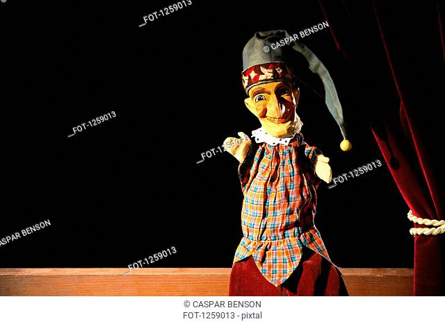 Punch from the classic puppet show Punch and Judy sitting on stage