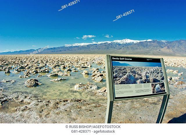 Interpretative sign on the flooded salt pan at Devil's Golf Course under Telescope Peak, Death Valley National Park, California