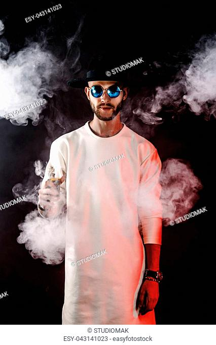 Handsome stylish man in hat and sunglasses with vapor