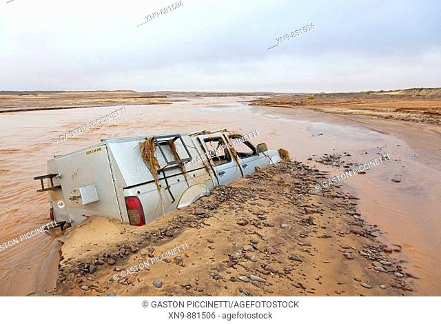 A car flowed and got stack due to the water increase of the Uniab river during the rainy season, Skeleton Cost Park, Namib desert, Namibia