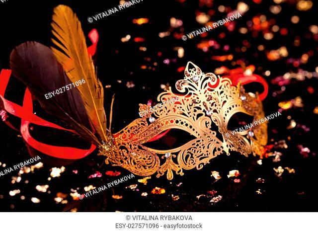 Gold carnival mask on black background