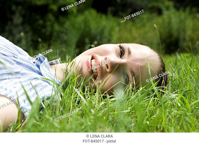 A young woman lying in grass