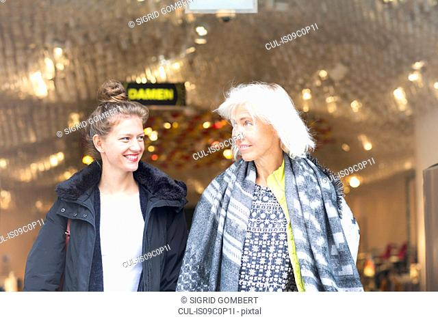 Mature woman and daughter leaving shop in city