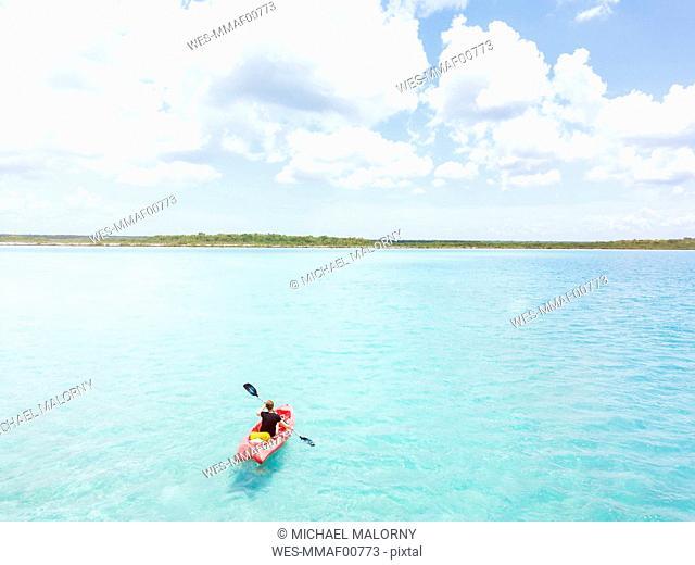 Mexiko, Yucatan, Quintana Roo, Bacalar, woman in kayak on the sea in turquoise water, drone image