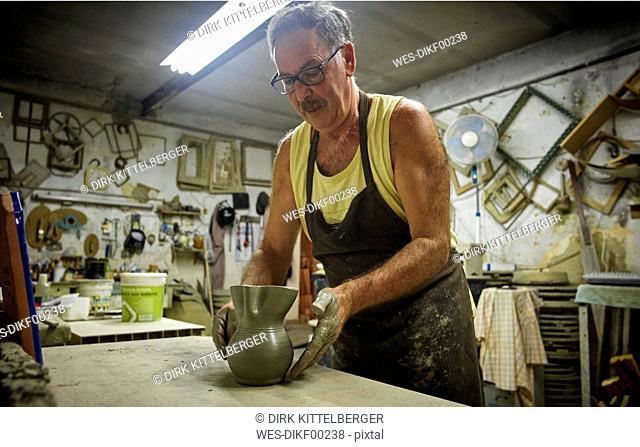 Potter in workshop placing earthenware jug on table before kilning
