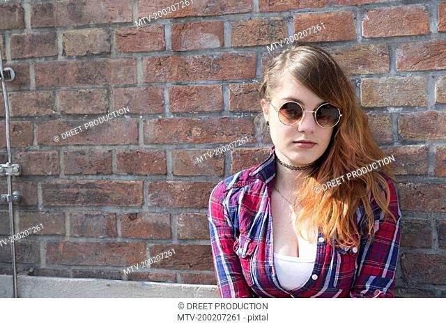 Young woman leaning in front of brick wall, Munich, Bavaria, Germany