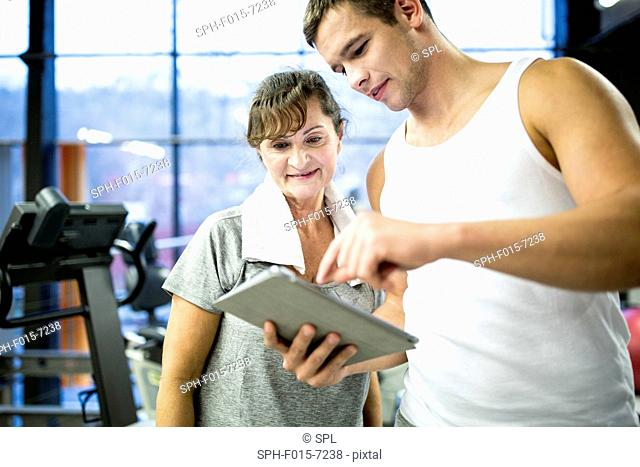 MODEL RELEASED. Trainer showing tablet to senior woman in gym