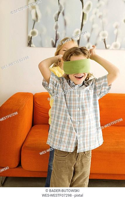 Boy 6-7 and girl 8-9 playing Blind Man's Bluff